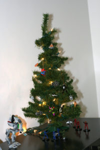 A small, green artificial tree. A LEGO chicken walker appears next to it as well as several space marine figurines.