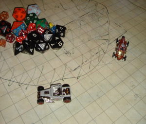 Matchbox cars -- small metal toys -- race on a grid map. A pile of dice appears in the upper-left corner.