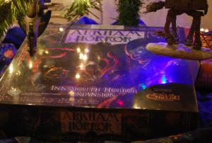 Christmas lights are reflected on the cover of the shrink-wrapped Innsmouth Horror board game.