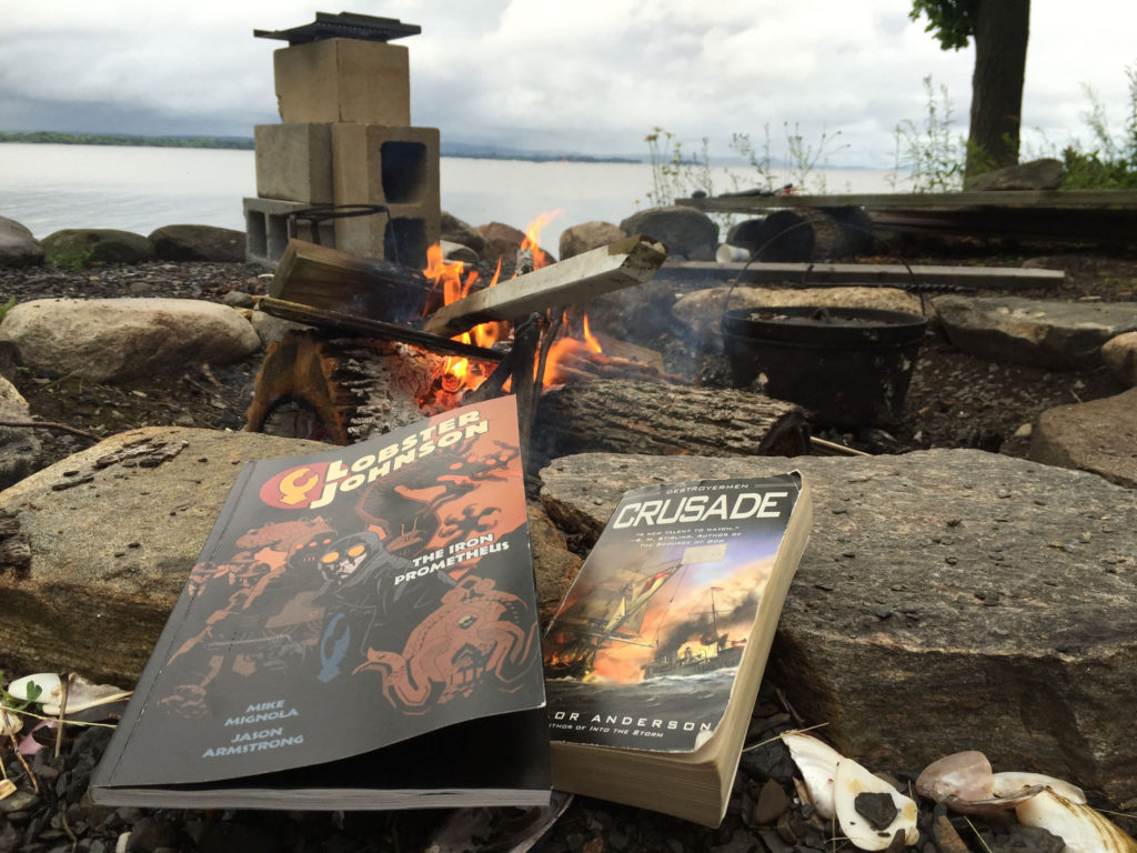 Two books -- Lobster Johnson and Crusade -- rest on rocks next to a fire pit. A fire can be seen burning in the upper portion of the photograph. The sky in the background is overcast.