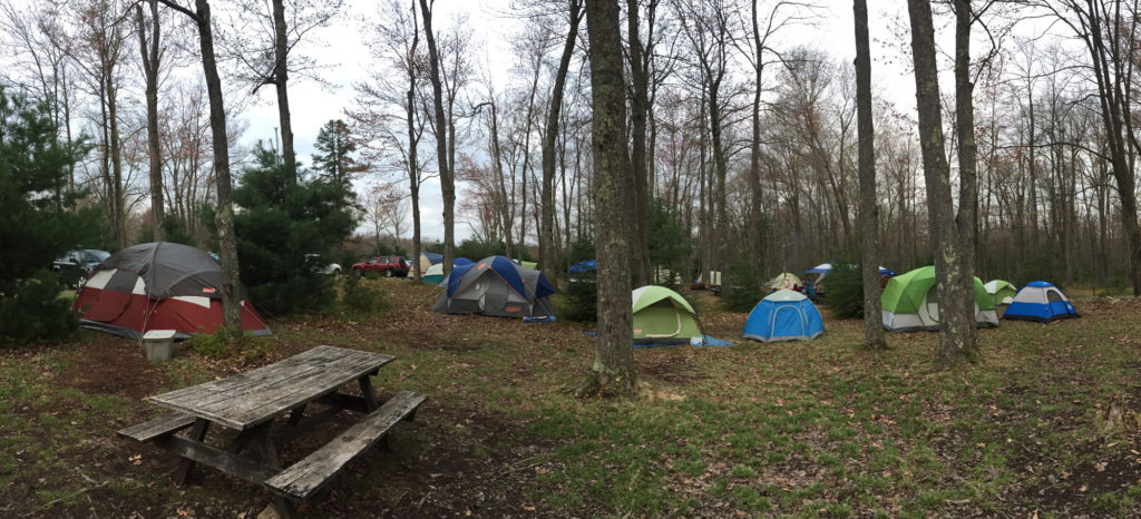 Several tents dot a campsite in early spring. A picnic table can be seen in the foreground.
