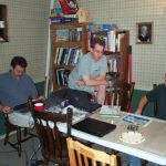 Three gamers sit at a gaming table, discussing the game.