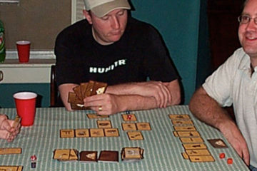 Gamers gathered around a table playing a card game.