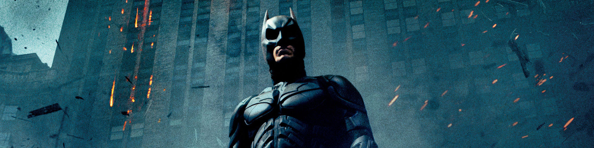 Batman, in his bat armor, stands in front of an office building. Smoke, ash, and cinders swirl through the air.