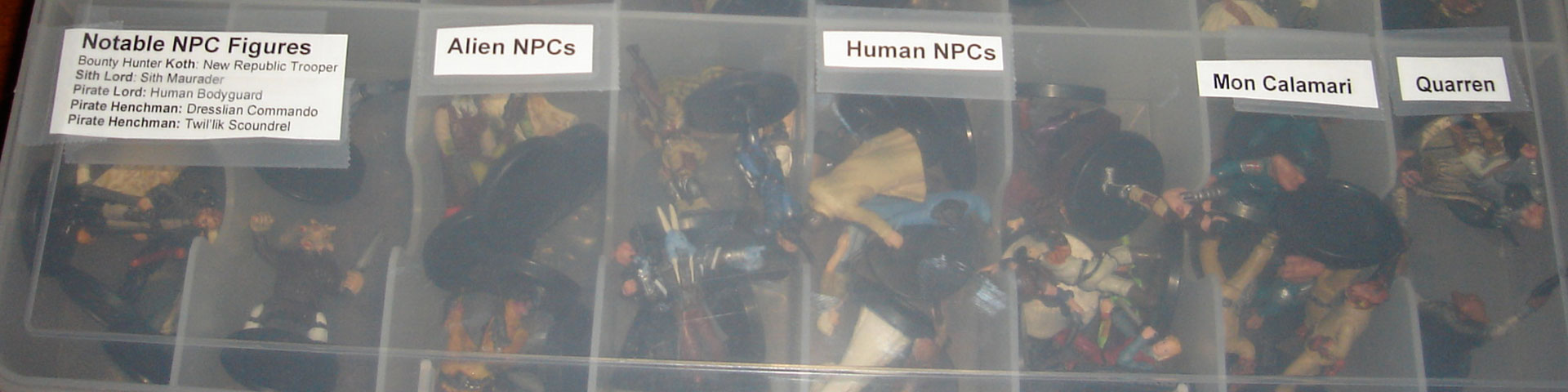 A plastic case with separate sections containing small plastic figurines. Each section is labeled.