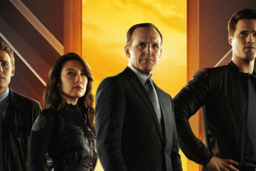 The 6 cast members of Season 1 stand in front the S.H.I.E.L.D. logo. The logo is split by a bright yellow/orange flame.