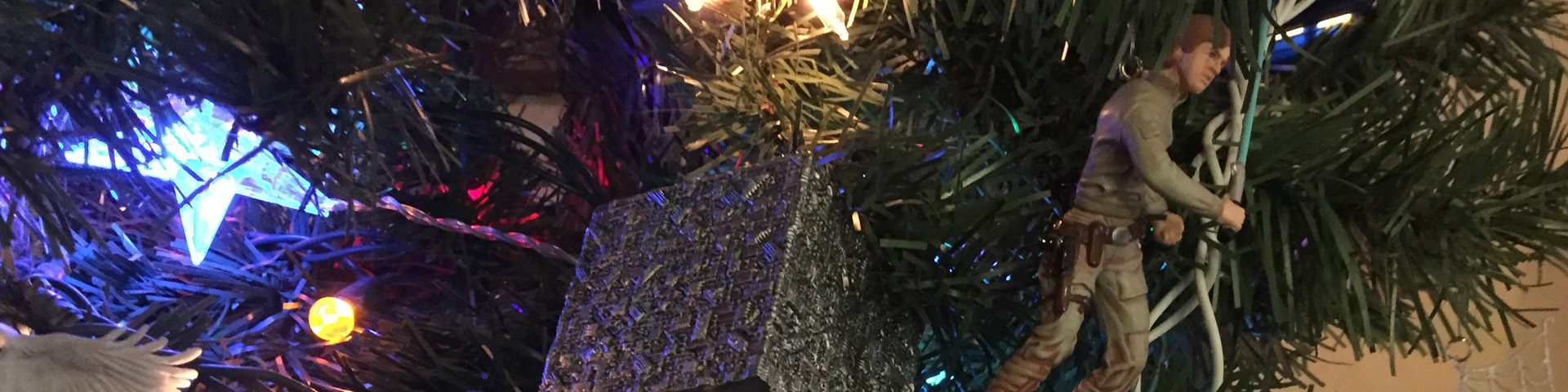 This close-up of the 2015 edition of the geek tree features IKEA star lights, the Borg Cube, and Luke Skywalker in his Bespin outfit.