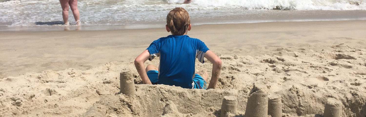 A sand castle fills the foreground while a 10-year-old boy sits just in front of it. The steel-blue ocean is in the background.