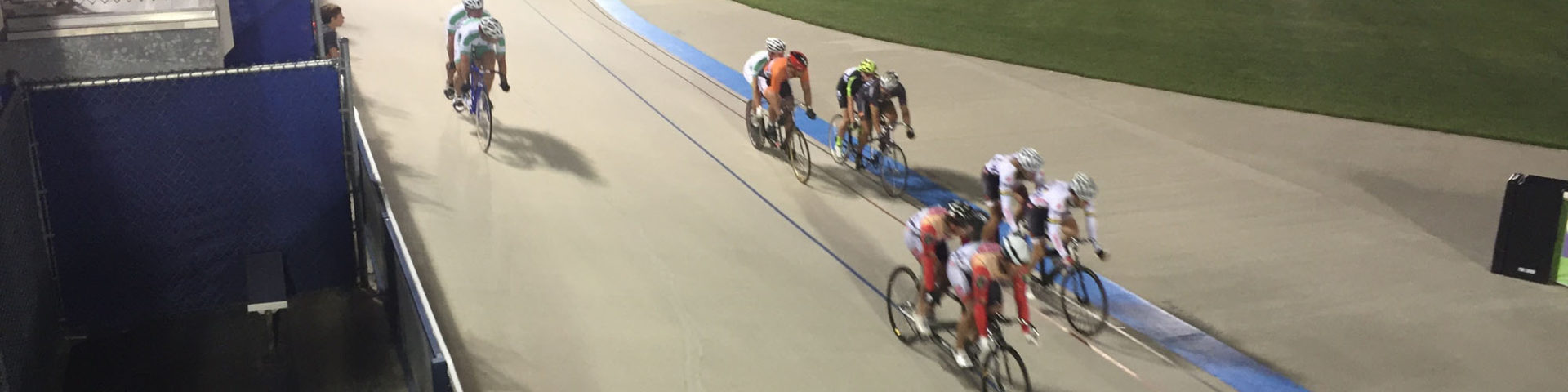 Cyclists race tandem bikes on an our door track.