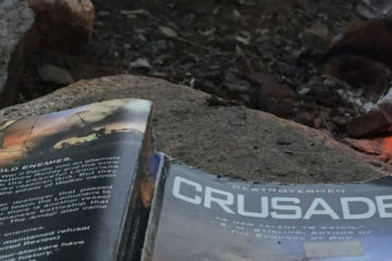 """The paperback book """"Crusade"""" lies face down on a rock next to a fire."""
