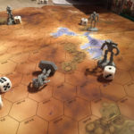 Four mechs battle on an orange-yellow hexagonal map. One of the mechs has been knocked down to represent it was badly damaged.