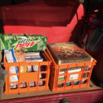 Two orange milk crates filled with role-playing game books, board games, and a case of Mountain Dew soda.