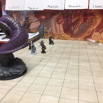 A large purple worm towers over several hero miniatures on a battle map.