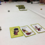 A hand of munchkin cards is laid out on a table.