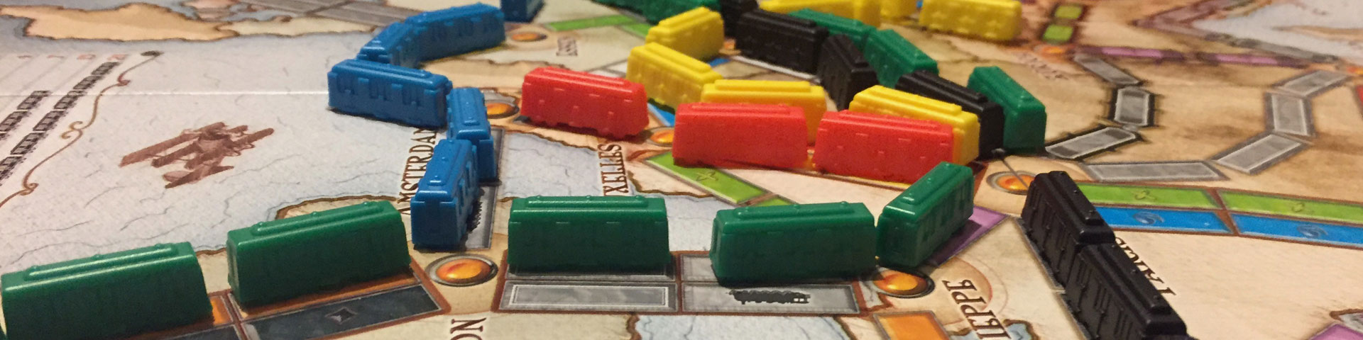 Multi-colored train pieces represent different routes that have been completed on the Ticket to Ride map.