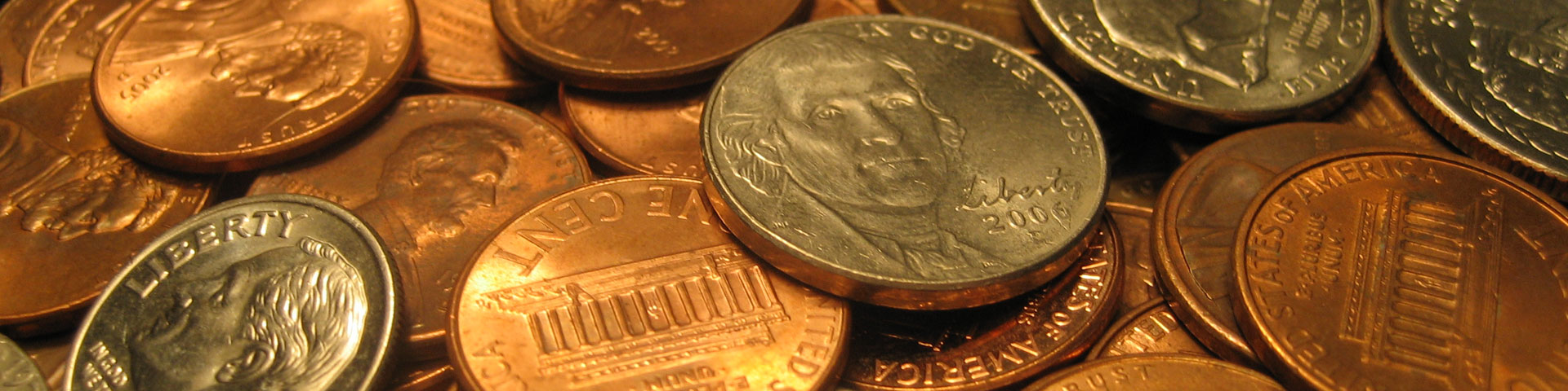 Numerous coins - pennies, nickels, and dimes - fill the photo.