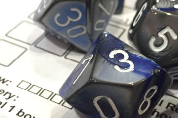 A close-up shot of blue-grey polyhedral dice on a Shadowrun character sheet.