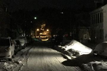 Streetlights illuminate a snowy street.