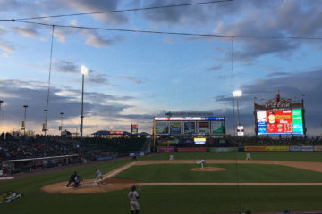 A minor league baseball park at sunset. The mostly blue sky is punctuated with clouds shading darker as the sun goes down.