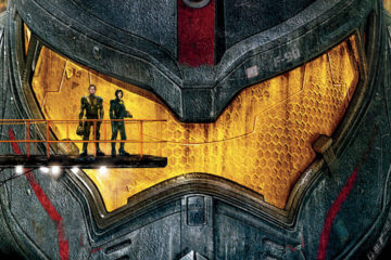 Two human figures stand in front of the yellow visor of a giant fighting robot.