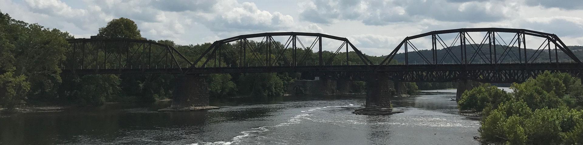 A large steel railroad bridge crosses a river.