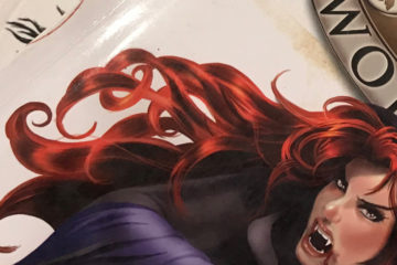 A stack of role-playing game books. A redheaded vampire appears on the cover of one them.