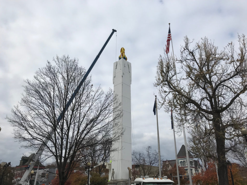 A crane puts the final touches on the Peace Candle in Easton's Centre Square. The candle is taller than the nearby flag poles and trees.