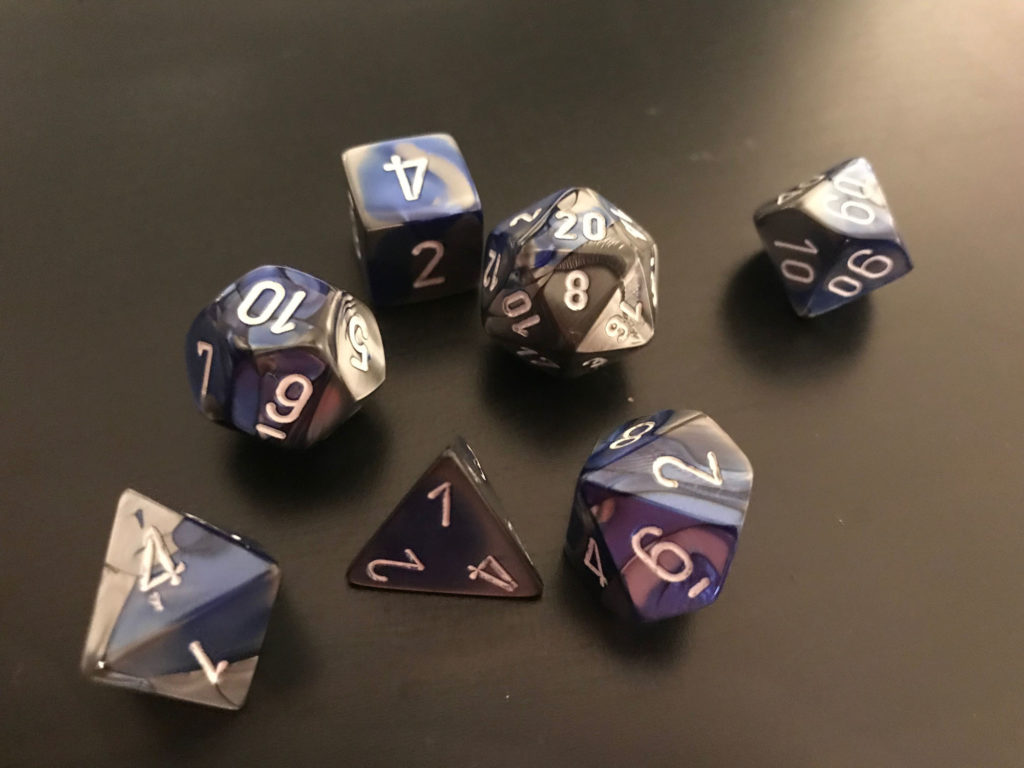 A set of blue-and-grey dice resting on a black background.