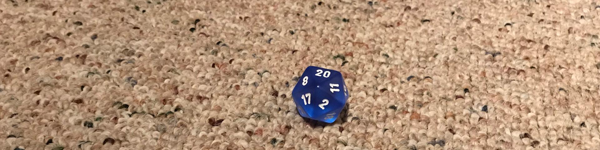 A single blue d20 rests on carpet.