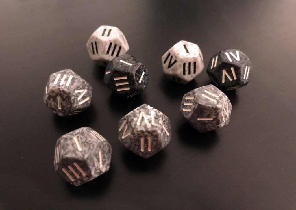 Different shades of grey twelve-sided dice, with the typical numbers replaced by Roman numerals.