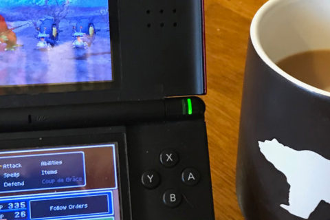 Dragon Quest IX appears on the screen of a Nintendo DS. Nearby is a mug filled with coffee.