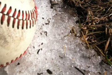A baseball sitting on snow next to a bare spot of ground.
